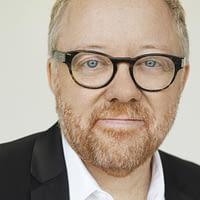 Homme barbu, aux yeux bleus, avec lunettes souriant