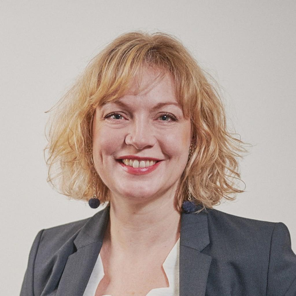 Femme blonde aux yeux bleus regardant et souriant vers la caméra.