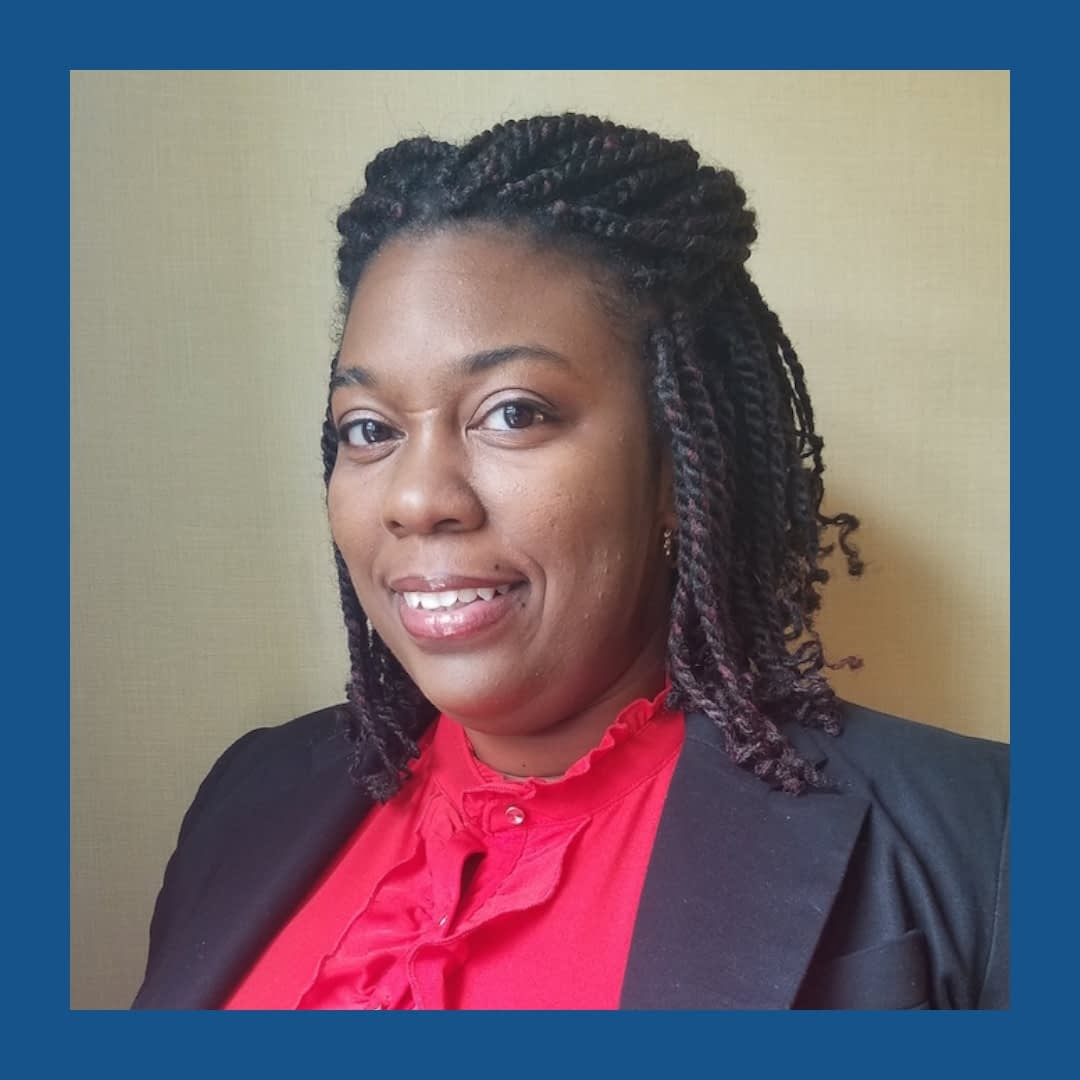 Black woman with braided hair, wearing a red shirt and dark blue blazer, looking and smiling at the camera. Navy blue frame.